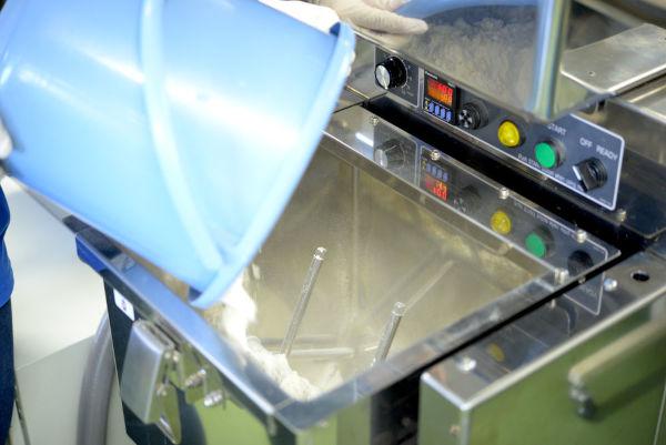 putting flour into noodle machine mixer