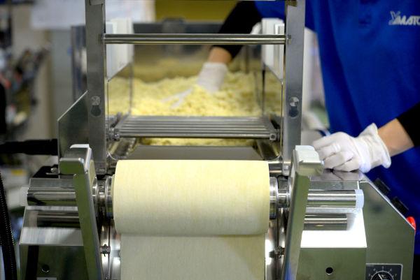 feeding dough mix into a gap between rollers on a ramen machine