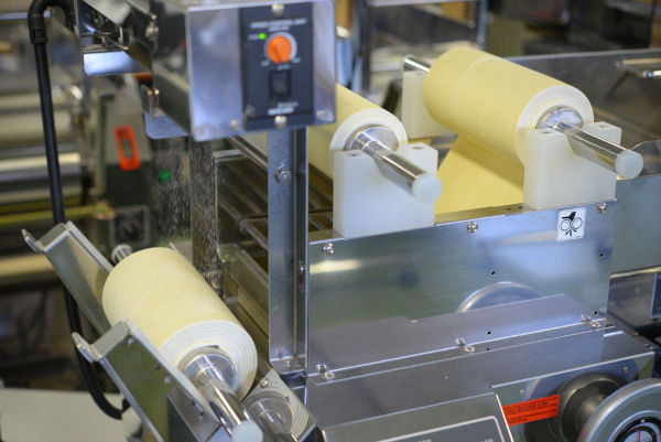 automatic duster sprinkling flour onto a dough sheet during production of ramen noodles on a ramen machine