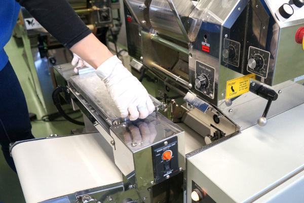 setting up a flour duster onto an automatic noodle portion conveyor of a ramen machine